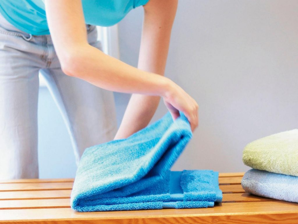 Woman-folding-a-towel-for-storage